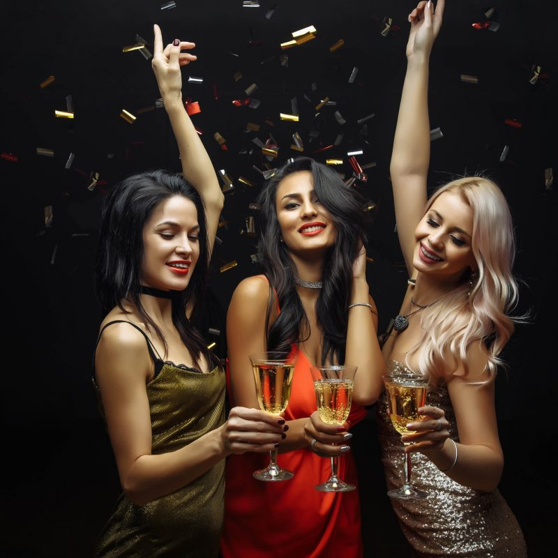 Young attractive women celebrating a party, drinking champagne and dancing.